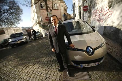 Carlos Ghosn, chairman and chief executive officer of French carmaker Renault, poses next to a Renault Zoe new electric car after a meeting with journalists in downtown Lisbon.