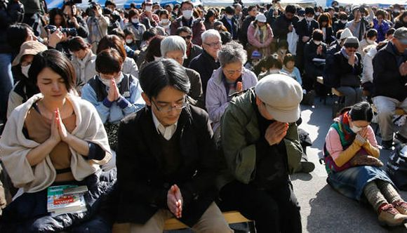 People observe a moment of silence during a rally after the magnitude 9.0 earthquake struck off Japan's coast.