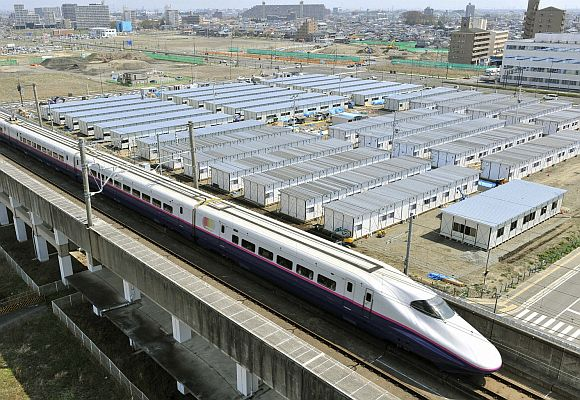 The Shinkansen, or bullet train, is seen speeding past temporary houses.