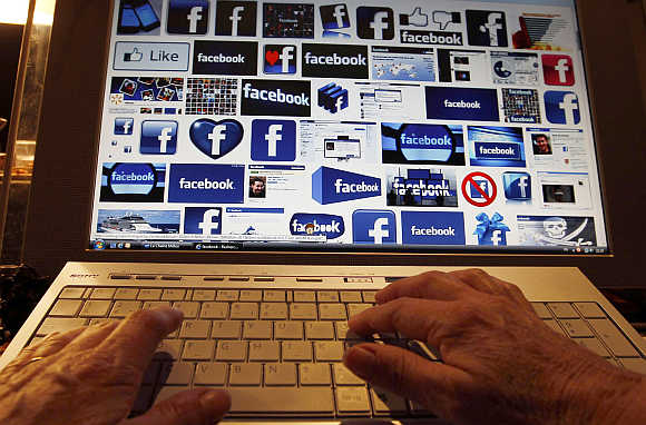 A woman works with her computer which displays Facebook logos on the screen in Bordeaux, Southwestern France.