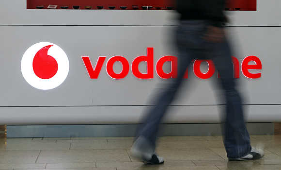 A customer walks past the Vodafone logo in a shopping mall in Prague, the Czech Republic.