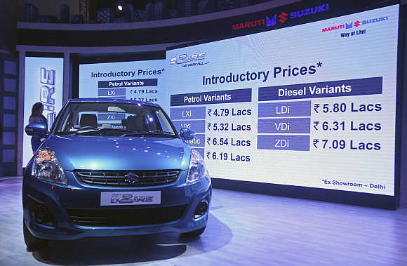 Prices of Maruti Suzuki's Swift Desire are flashed on a screen during its launch in New Delhi.
