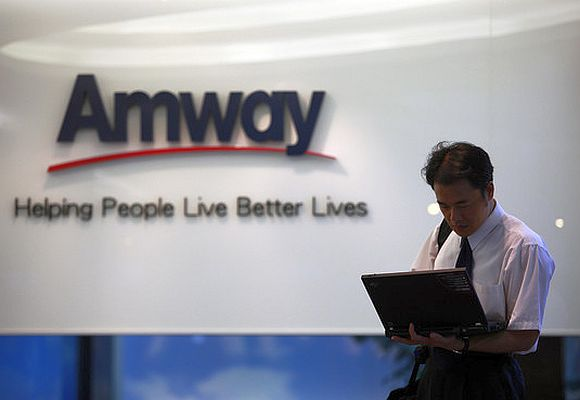 A man looks at his laptop outside Amway's sales showroom.