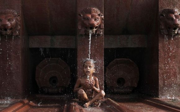 A boy cools himself off as he sits under a fountain on a hot summer day in New Delhi.
