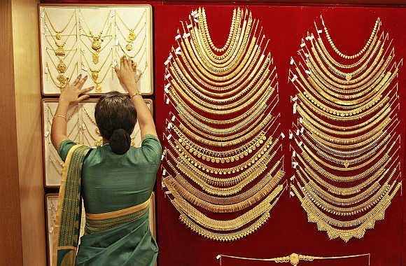A saleswoman arranges a gold necklace inside a jewellery showroom in Kochi.