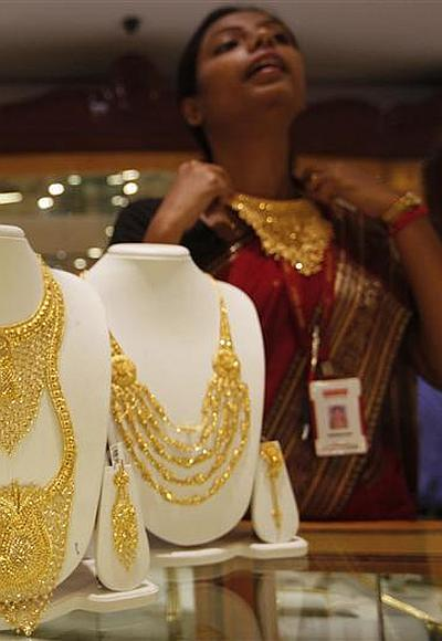 A saleswoman displays a gold necklace at a jewellery showroom.