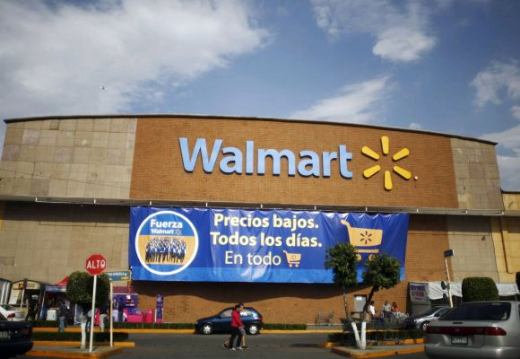 People walk past a Wal-Mart store with a banner reading ''Low prices, every day, in everything'' in Mexico City.