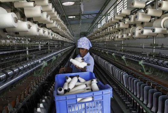 A worker handles the production of yarn on a yarn-spinning equipment at a factory.