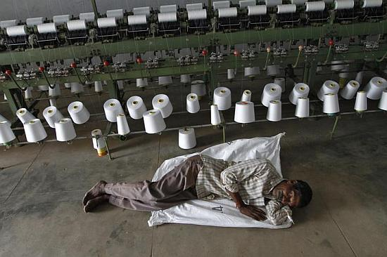 A worker takes a nap during a power cut in front of yarn-spinning equipment inside a factory.