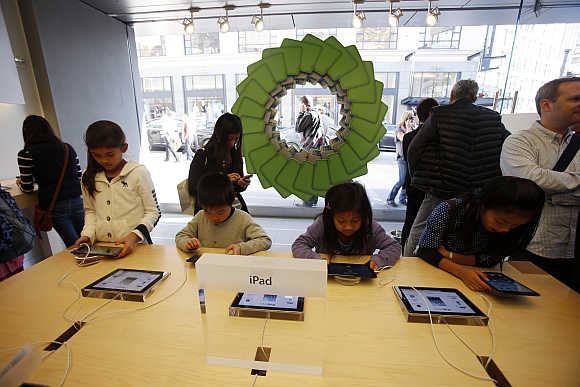 Young holiday shoppers interact with iPads at an Apple Store in San Francisco, California.
