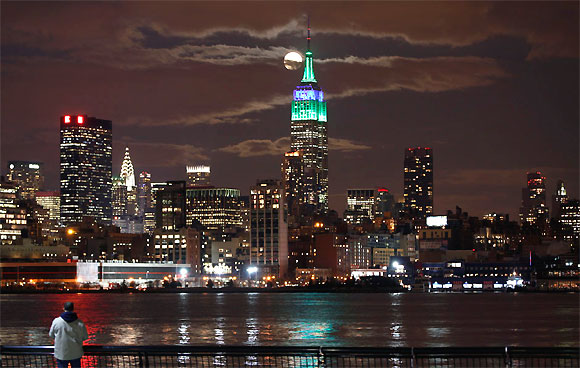 A full moon rises behind the Empire State Building in New York as a man watches in a park along the Hudson River in Hoboken, New Jersey.