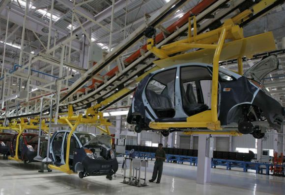 An employee stands inside the Tata Nano plant at Sanand.
