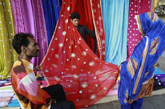 Men display fabric to a woman.