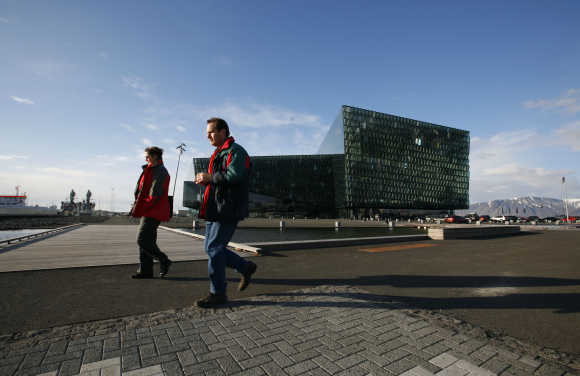People walk past Harpa Concert Hall in downtown Reykjavik, Iceland.