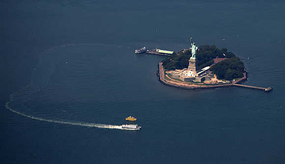 A passenger ferry leaves the The Statue of Liberty and Liberty Island seen from this aerial view over New York Harbor.
