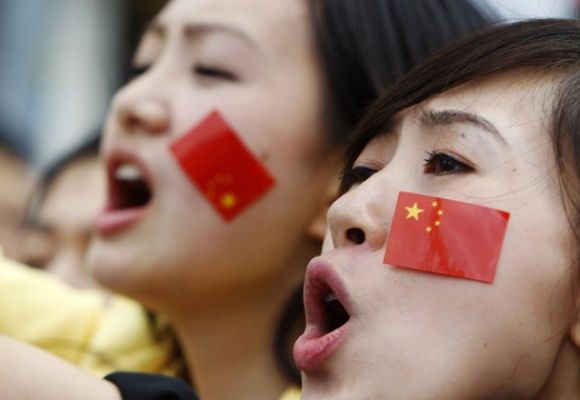 Members of the Chinese community with stickers of the Chinese flag stuck on their faces.