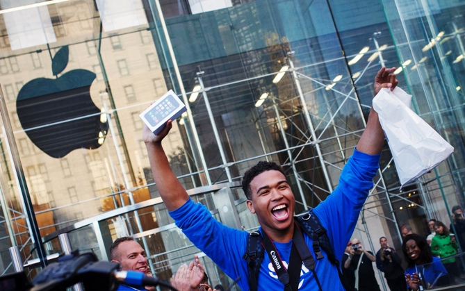 One of the first customers to purchase the Apple iPhone 5S celebrates after exiting the Apple Retail Store on Fifth Avenue in Manhattan, New York.