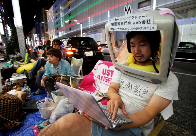 A man wearing an iMac on his head waits for the release of Apple's new iPhone 5S, near the Apple Store at Tokyo's Ginza shopping district.