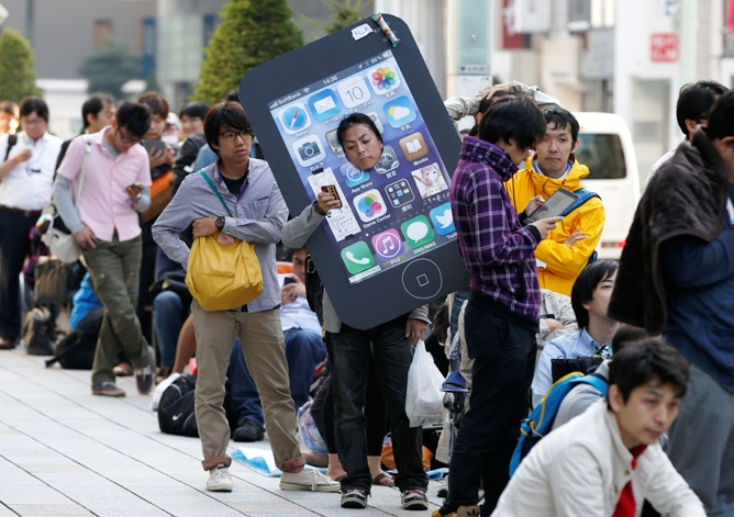 An iPhone fan waits outside an Apple Store to purchase Apple's new iPhone 5S at Tokyo's Ginza shopping district.