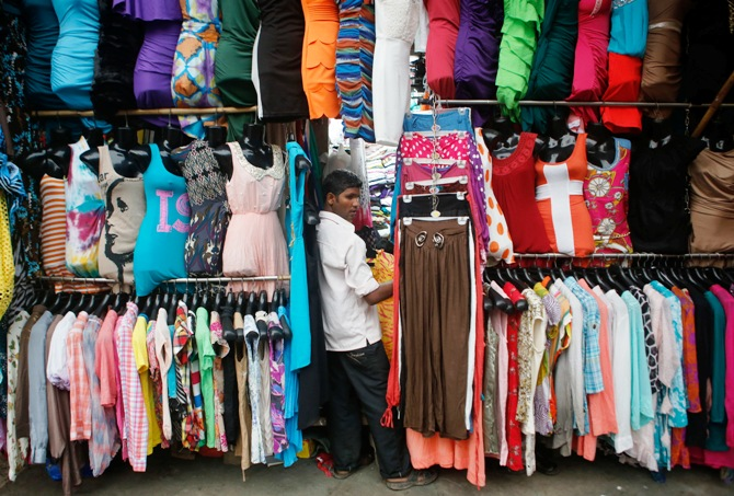 A salesman waits for customers at a roadside store selling clothes at a market in Mumbai.