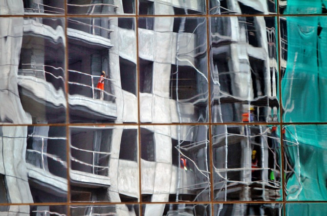 A residential building undergoing construction is reflected on the glass facades of a commercial complex in Chennai.