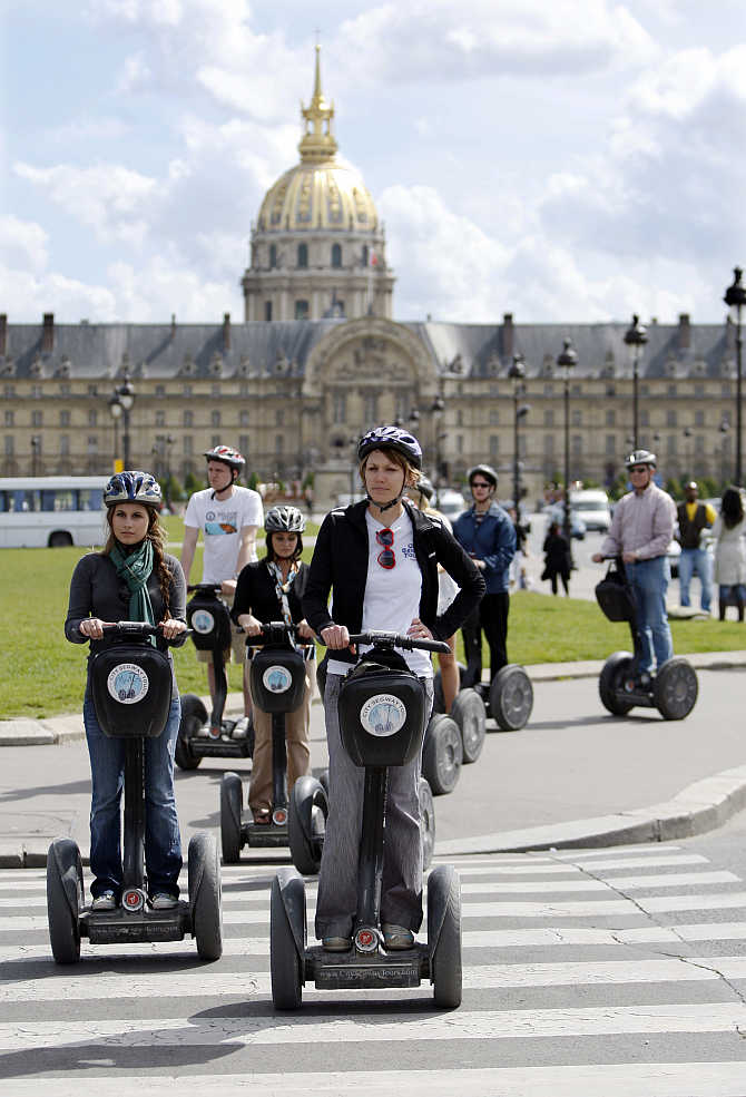 A group of tourists take in the sights of Paris in front of the Invalides on Segways, France.