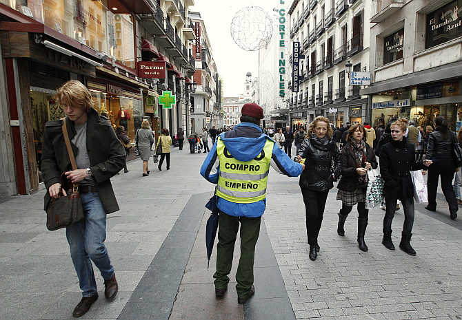 A pawn shop employee distributes leaflets in downtown Madrid, Spain.