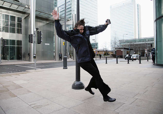 A woman is blown off her feet by the wind in Canary Wharf, London's financial district, United Kingdom.