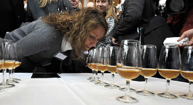 A woman smells samples of champagne from one of the 168 bottles salvaged from a 200-year-old shipwreck near the waters of Aland Islands after it was opened in Mariehamn, Finland.