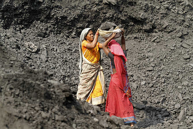 Labourers carry coal at a stockyard of an underground coal mine in the Mahanadi coal fields at Dera near Talcher in Orissa. Photo is for representation purpose only.