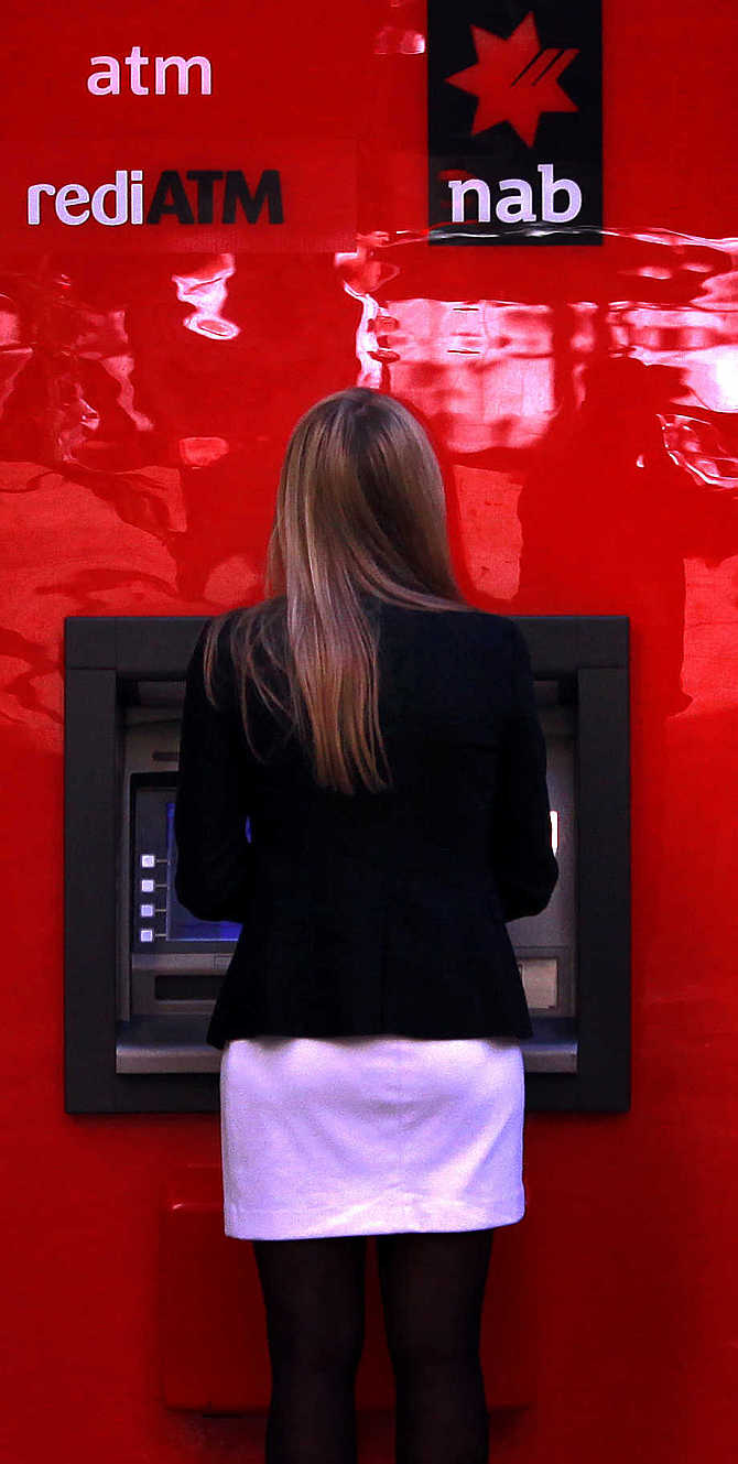 A woman uses a National Australia Bank's ATM in central Sydney, Australia.