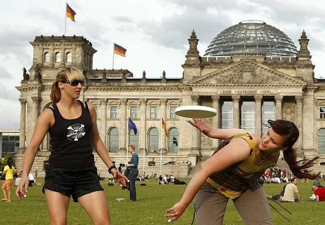 Women play with a frisbee in front of the Reichstag building in Berlin, Germany.