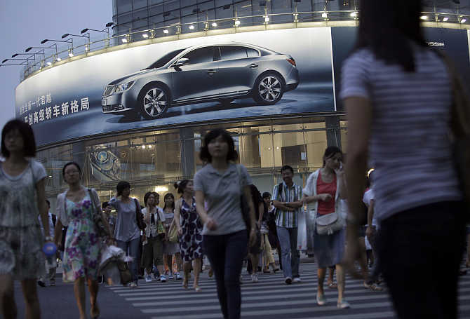 People cross a road in front of a car dealer shop in downtown Shanghai, China.