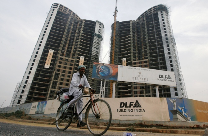 A file photograph shows a man cycles past the construction site of a residential apartment building by Indian property developer DLF Ltd. in Gurgaon.