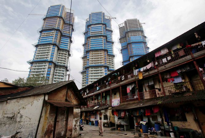 This file photograph shows high-rise residential towers under construction are pictured behind an old residential building in central Mumbai.