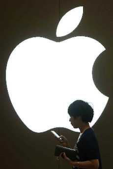 A woman looks at the screen of her mobile phone in front of an Apple logo outside its store in downtown Shanghai, China.
