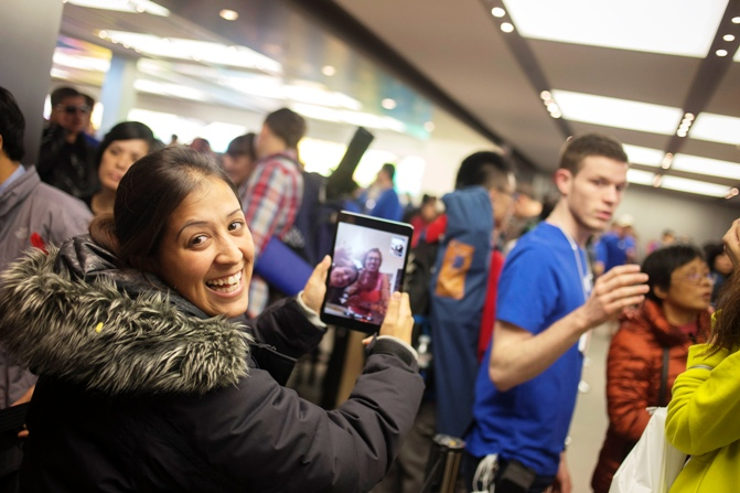 Shirly Tishler of Israel uses an iPad mini to speak to her family back home as she awaits in line to purchase the new Apple iPhone 5S phone at the Apple Retail Store o