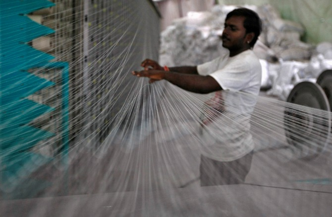 An employee works at the production line of Rajnagar textile mill in the western Indian city of Ahmedabad.