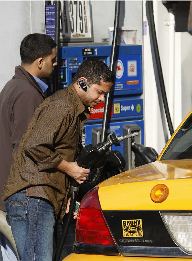 A taxi driver fills his cab at a petrol pump on Manhattan's West Side in New York.