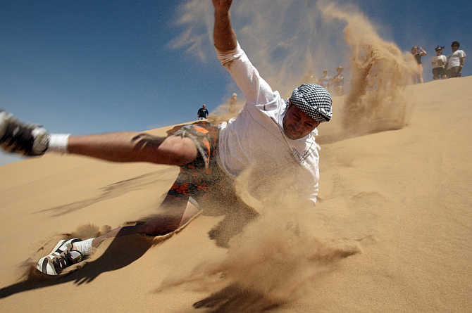 A tourist enjoys sand surfing near the Dakhla oasis in Egypt's Western Desert, some 900km southwest from Cairo.