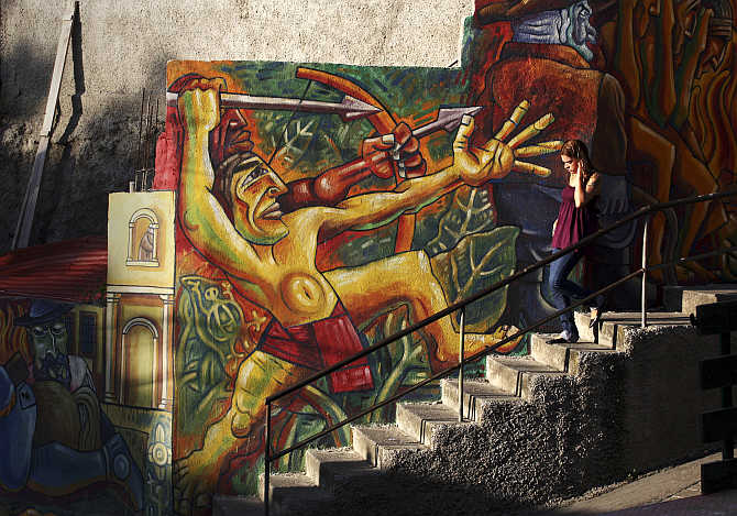 A girl walks past a mural in the neighbourhood of La Pastora in Caracas, Venezuela.