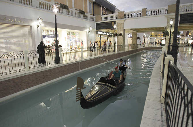 A man takes a boat ride through a canal inside Villagio Mall, a popular shopping area in Doha's west end, Qatar.