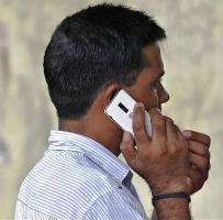 A man speaks on a mobile phone.