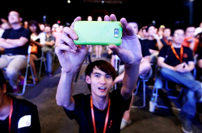 A user of Xiaomi uses his mobile phone to take a photo at a launch ceremony of Xiaomi Phone 2 in Beijing.