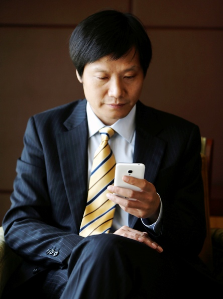 Lei Jun, founder and CEO of China's mobile company Xiaomi, checks his Xiaomi mobile phone.