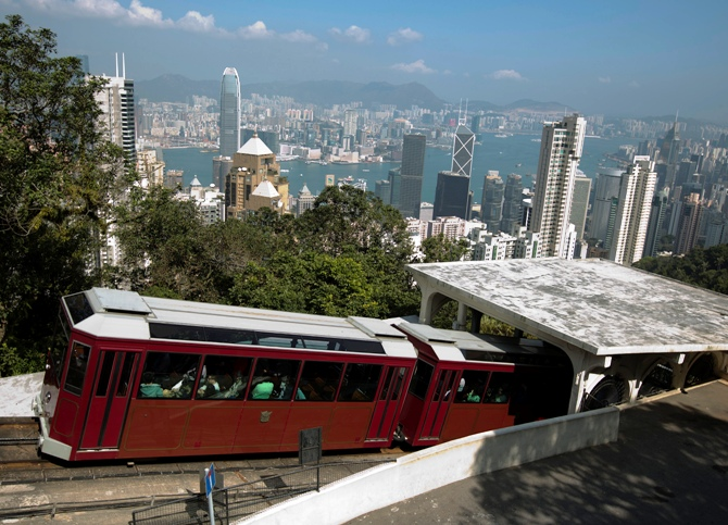 A peak tram passes a tram station on Hong Kong island.