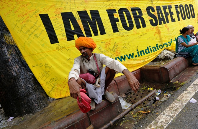 A farmer squats along a footpath near a banner during a day-long protest in New Delhi.