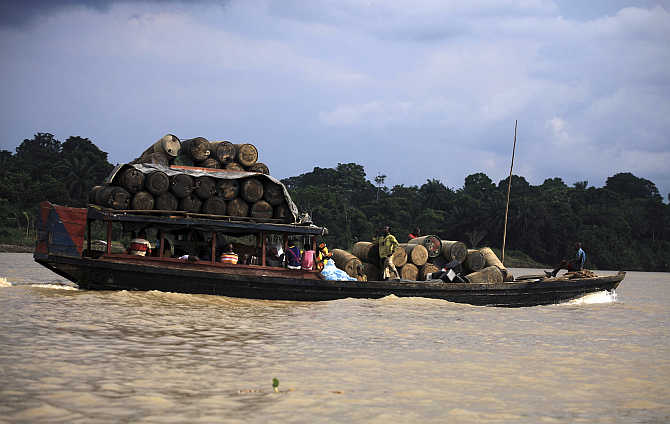 People travel on a locally built passenger boat loaded with oil containers through a creek on the River Nun in Nigeria's oil state of Bayelsa.
