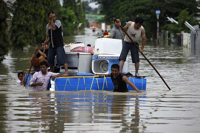 Residents carry their belongings on a makeshift raft at a housing area in Karawang, Indonesia's West java province, after floods caused Citarum River to overflow.