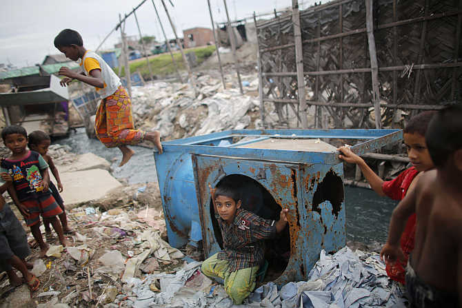 Children play around discarded items at the Hazaribagh area in Dhaka, Bangladesh.